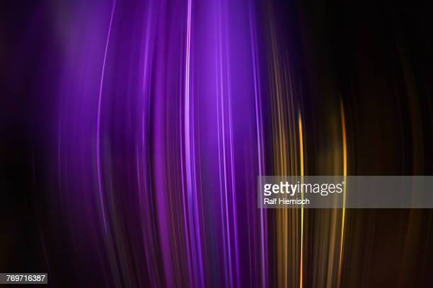 full frame abstract image of purple and golden light trails - gold rush stock-fotos und bilder