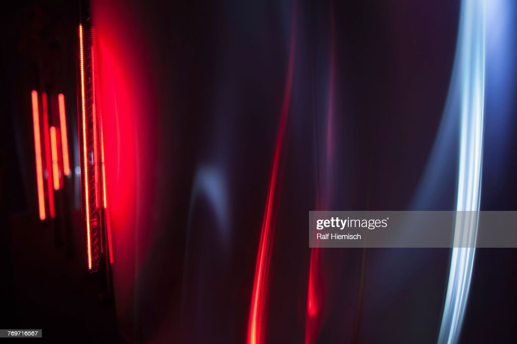 Full frame abstract image of red and gray light trails against black background : Stock Photo