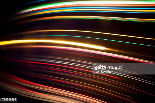 Full frame abstract image of various light trails against black background