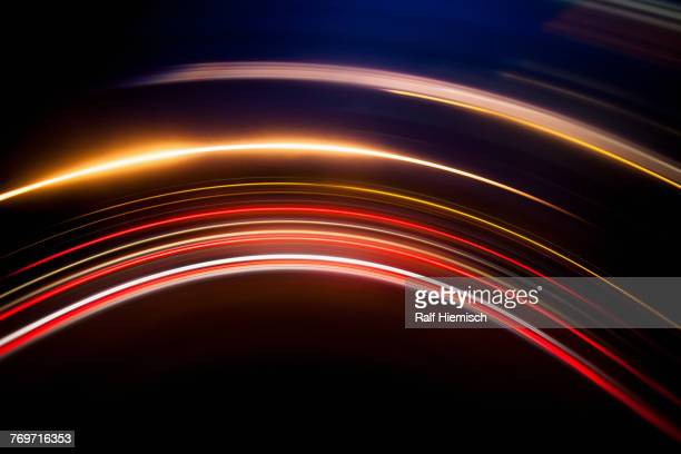 full frame abstract image of vibrant light trails against black background - gold rush stock-fotos und bilder