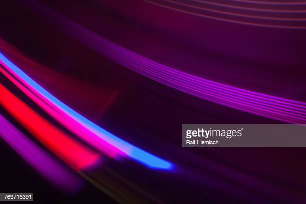 Full frame abstract image of vibrant purple and red light trails
