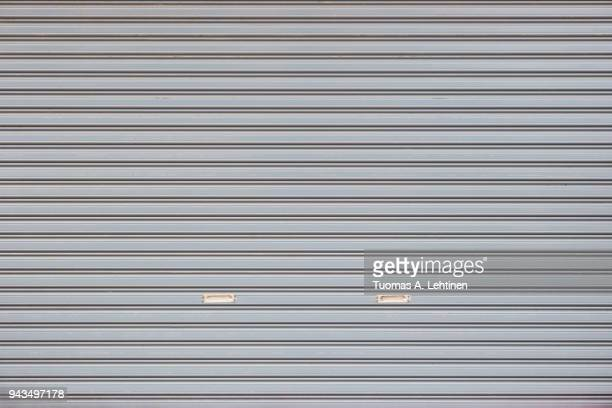full frame background of a closed roller door (or roller shutter, sectional overhead door, roll up or garage door). - industrial door stock pictures, royalty-free photos & images