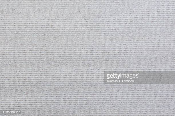 Full frame background of a light, almost white, carpet viewed from above.