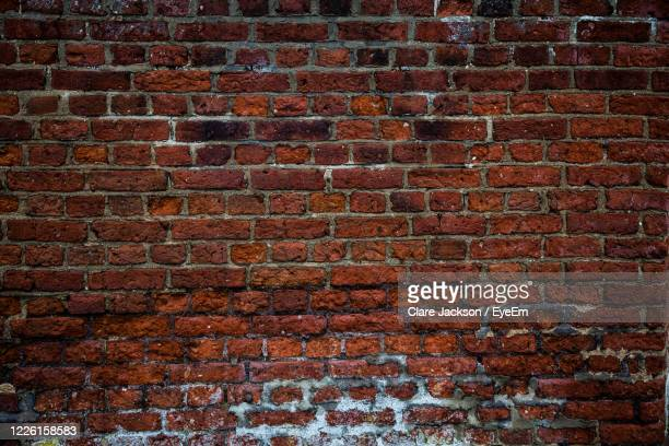 a full frame background of a rough and textured brick wall with visible wear and tare and copy space - brick wall stock pictures, royalty-free photos & images