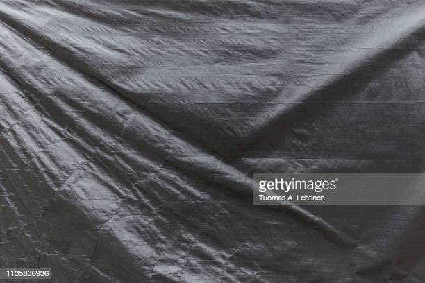 full frame background of a wrinkled gray tarp texture - tarpaulin stock pictures, royalty-free photos & images