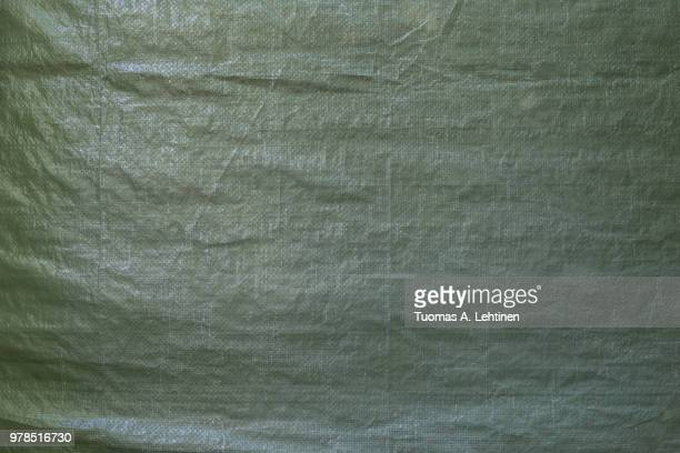 full frame background of a wrinkled green tarp texture - tarpaulin stock pictures, royalty-free photos & images