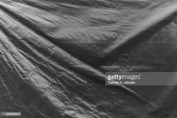 full frame background of a wrinkled tarp texture in black and white. - tarpaulin stock pictures, royalty-free photos & images