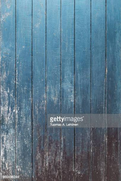 Full frame background of an old and faded wood board wall painted in blue