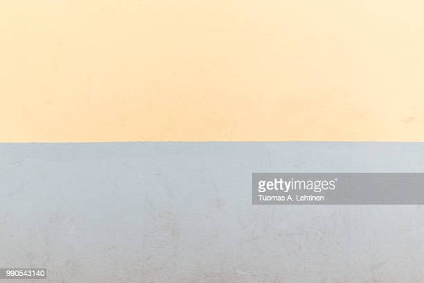 Full frame background of an old concrete wall painted in light yellow and gray