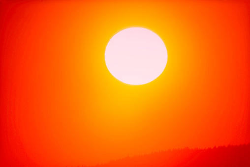 Full frame, Close-up of a big orange sun setting above the rainforest of southern British Columbia - gettyimageskorea