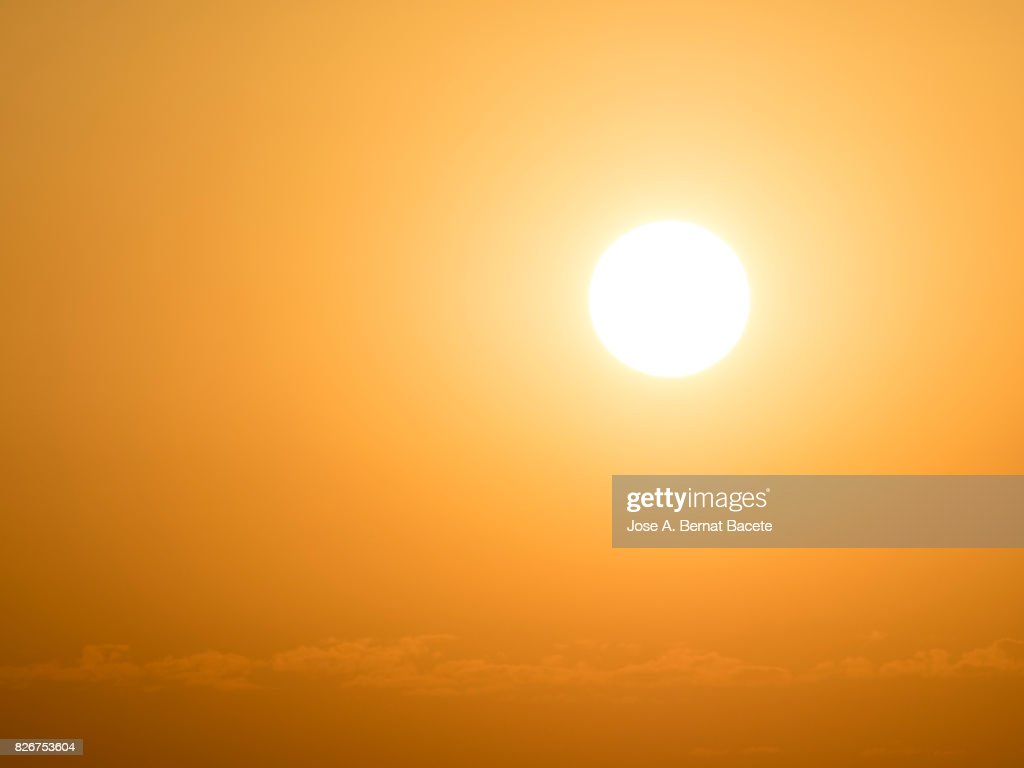 Full frame glowing sun at sunset with an orange and yellow sky : Stock-Foto