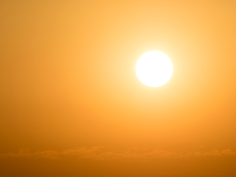Full frame glowing sun at sunset with an orange and yellow sky - gettyimageskorea