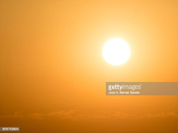 full frame glowing sun at sunset with an orange and yellow sky - luz del sol fotografías e imágenes de stock