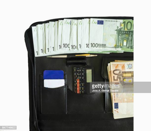 Full frame Interior of a business black briefcase with heaps of tickets of Euro, cards of credit and a calculator