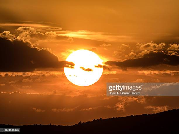 full frame of a beautiful colorful orange sky with clouds at sunset - suns stock photos and pictures