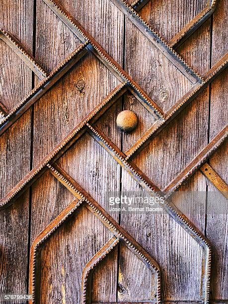 Full frame of a detail of an old wooden door with metallic trim
