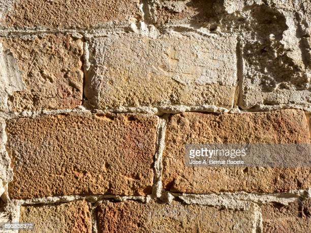Full frame of a facade of a cement wall with bricks  ancient and spoil in the time.  Outdoors illuminated by the lateral light of the Sun. Spain.