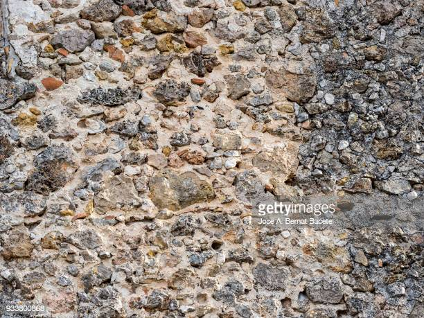 Full frame of a facade of a stone wall with bricks ancient. High resolution photography.