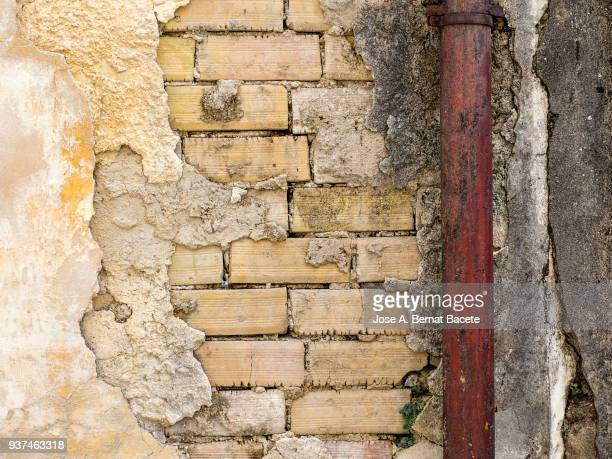 Full frame of a facade of a wall of old bricks and a gutter of outlet of rain. High resolution photography.