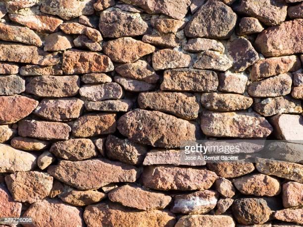 full frame of a facade of a wall of stone constructed with volcanic rocks of origin - muro de pedra - fotografias e filmes do acervo