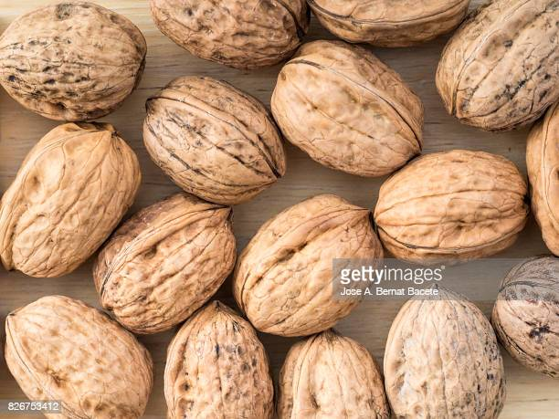 full frame of a group of walnuts on a wooden table. spain - nutshell stock photos and pictures