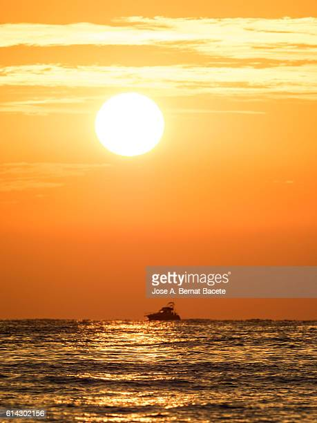 Full frame of a sunrise of orange, with the sun rising from the waters of the sea and the silhouette of a pleasure yacht.