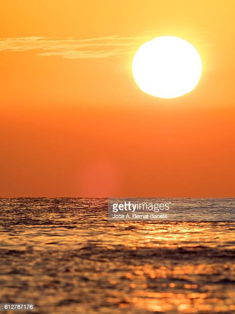 Full frame of a sunrise, with the sun rising from the waters of the sea and orange clouds. Spain