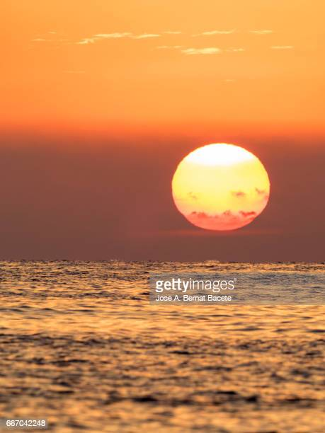 Full frame of a sunset Sun with high clouds of colors orange, next to sea water