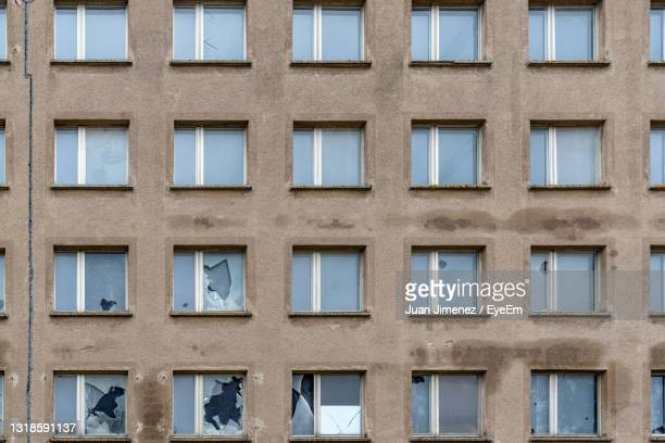 full frame of array of windows with broken glass in old building facade. island of rugen. - extremism stock pictures, royalty-free photos & images