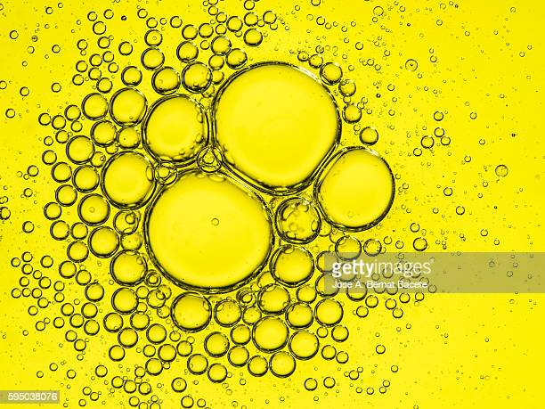 Full Frame of circular bubbles floating on water yellow