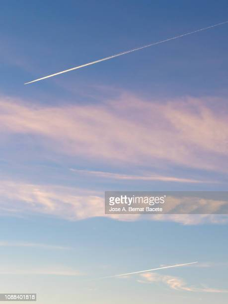 full frame of clouds of colors in sky during sunset with the stele of smoke of a plane crossing the sky. - trainée d'avion photos et images de collection