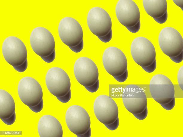 full frame of eggs on yellow background - ivf stock pictures, royalty-free photos & images