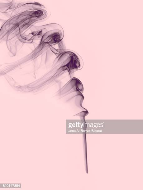Full frame of forms and figures of smoke of color gray in ascending movement on a vintage pink background
