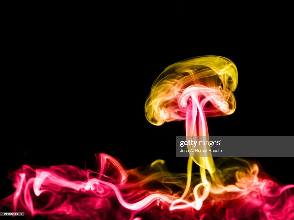 Full frame of forms and figures of smoke of colors yellow and red in ascending movement produced, by an explosion on a black background : Stock Photo