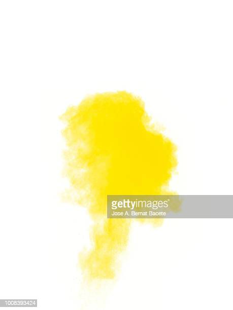 Full frame of forms and textures of an explosion of powder and smoke of color yellow on a white background.