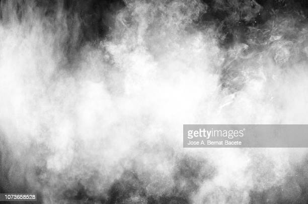 full frame of forms and textures of an explosion of powder and smoke of color white and gray on a black background. - smoking activity stock pictures, royalty-free photos & images