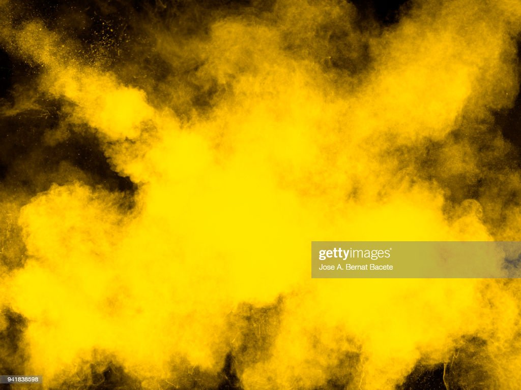 Full frame of forms and textures of an explosion of powder and smoke of color yellow and white on a black background : Stock Photo