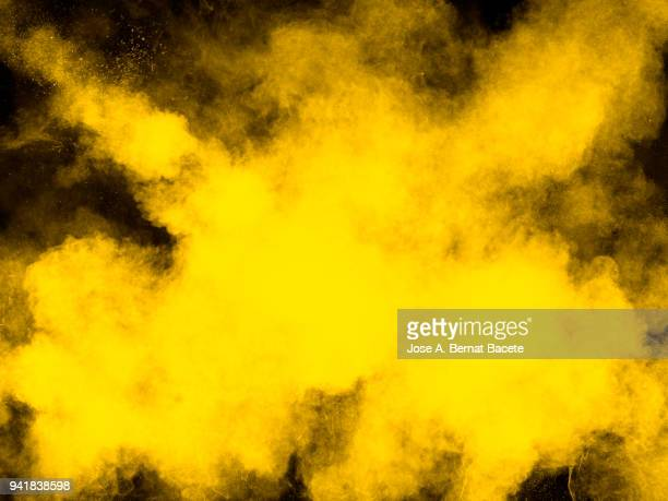 full frame of forms and textures of an explosion of powder and smoke of color yellow and white on a black background - yellow photos et images de collection