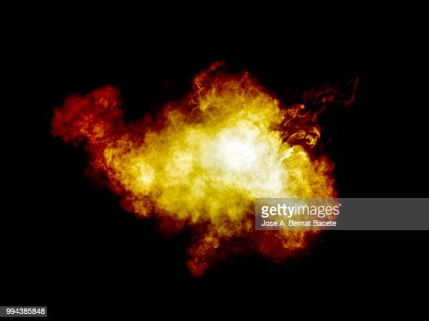 Full frame of forms and textures of an explosion of powder and smoke of color yellow and red on a black background.