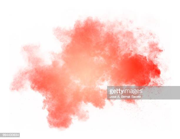 Full frame of forms and textures of an explosion of powder and smoke of color red and orange on a white background.