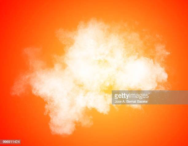 Full frame of forms and textures of an explosion of powder and smoke of color white and yellow on a orange background.