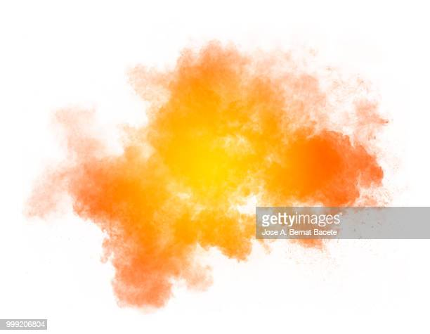 Full frame of forms and textures of an explosion of powder and smoke of color yellow and orange on a white background.
