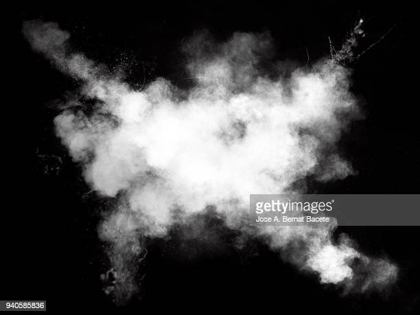 Full frame of forms and textures of an explosion of powder of color white on a black background.