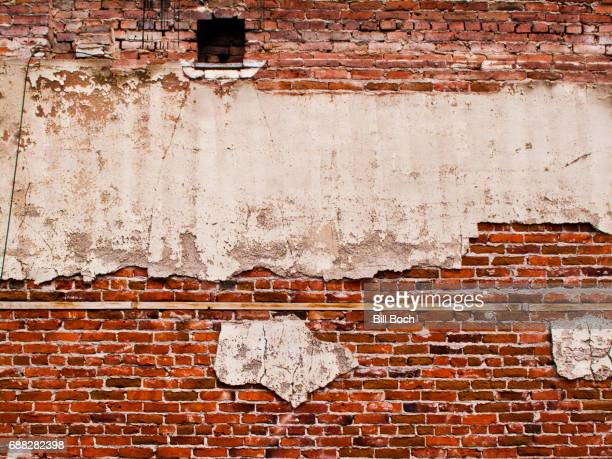Full frame of old 1920's brick and stucco wall with mysterious dark opening