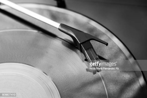 full frame of record player needle on the record. directly above and copy space - groove stock photos and pictures