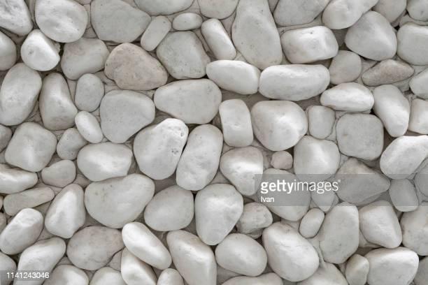 full frame of texture, white cobble pebbles stone - adoquinado fotografías e imágenes de stock