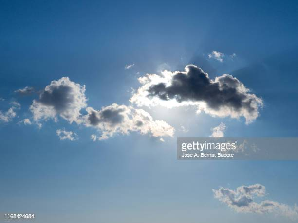full frame of the blue sky with bright sun and white clouds. - midday stock pictures, royalty-free photos & images