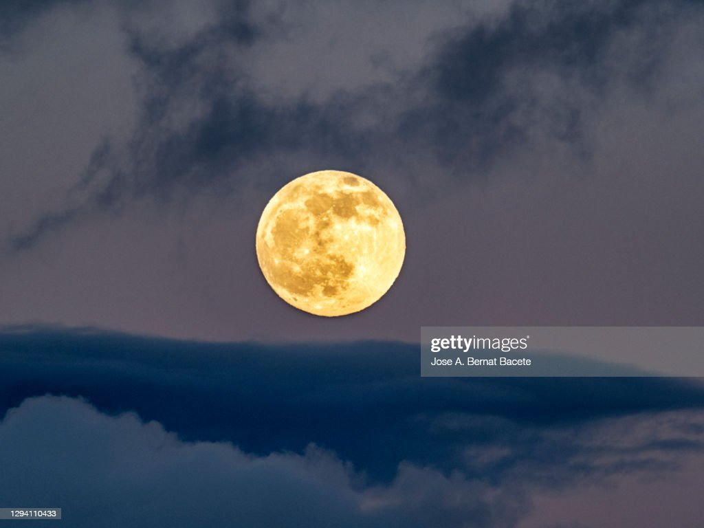 Full frame of the full moon at sunset with a sky with clouds. : Stockfoto