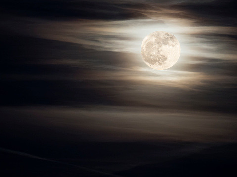 Full frame of the full moon of yellow color on a sky with some high clouds (winter solstice). - gettyimageskorea