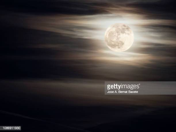 full frame of the full moon of yellow color on a sky with some high clouds (winter solstice). - luna nera foto e immagini stock